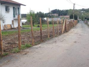 Pose de piquets d'acacia pour tenir la future clôture en brande de bruyère